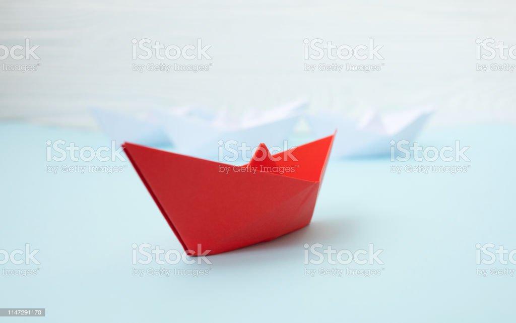Paper ship on blue background. Conversation concept.
