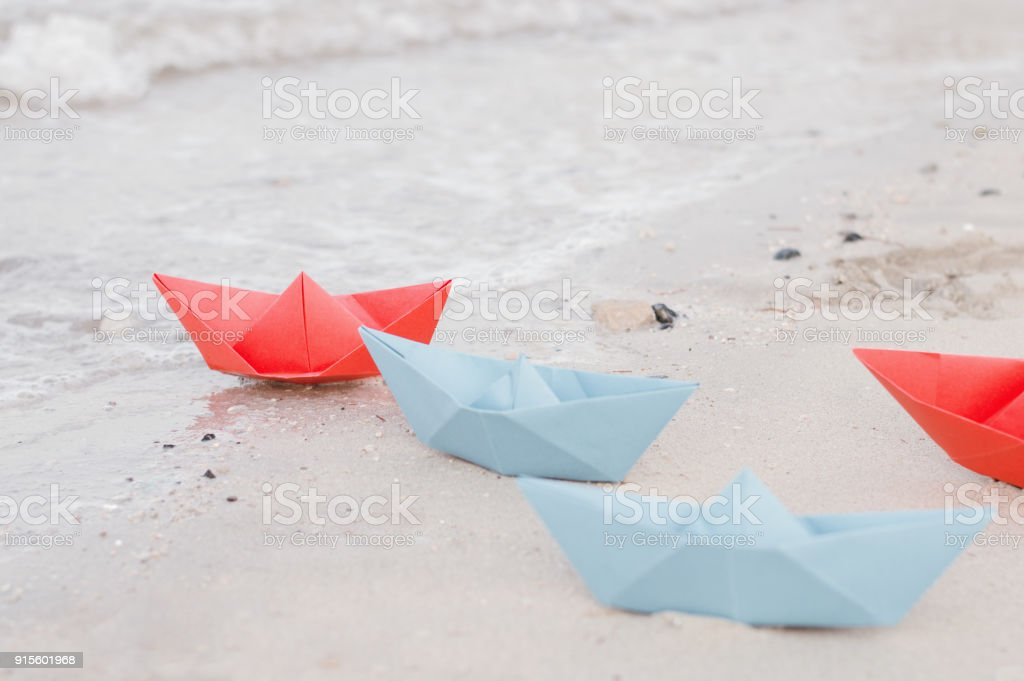 Paper ships of blue and red color on sandy beach near water waves....