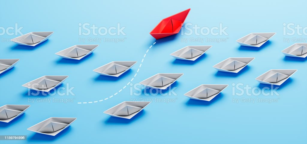 Gruppe von weißen Papierschiffen auf Untergrund mit einzelnem rotem...