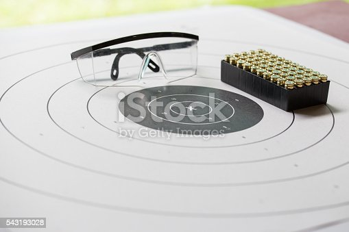 istock paper shooting target with safety glasses and 9 mm bullet 543193028