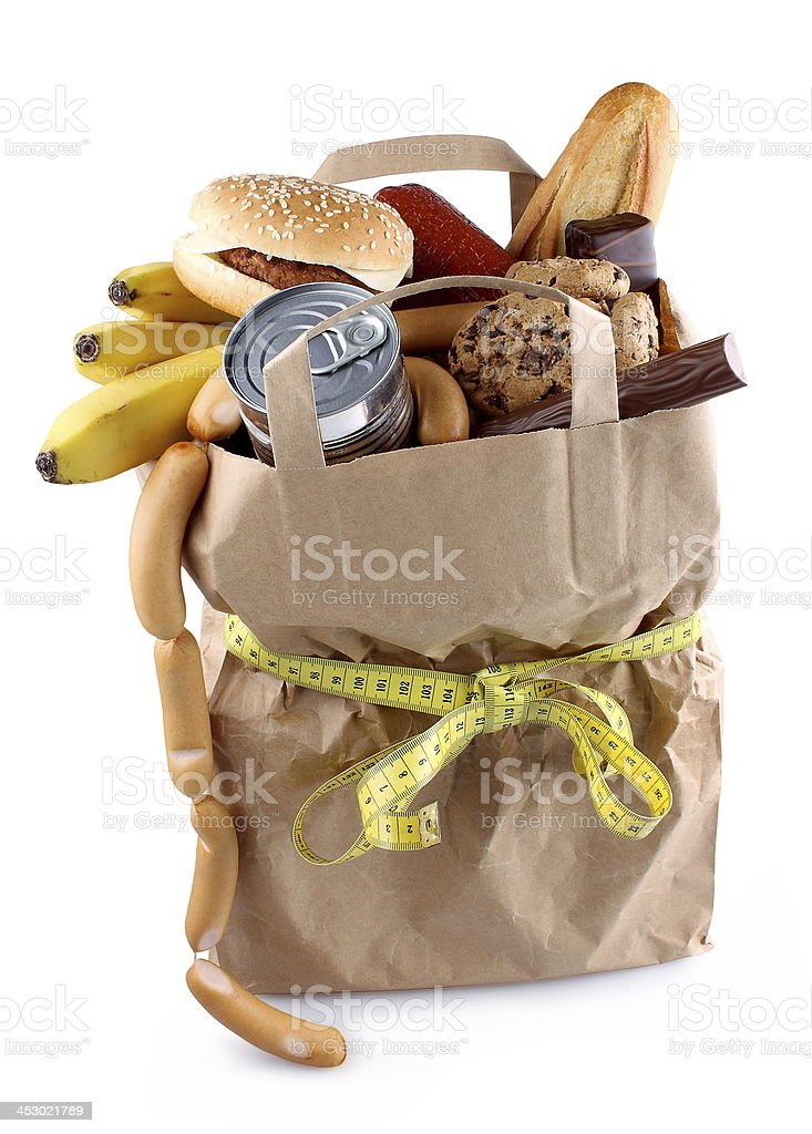 Paper shopping bag with high-calorie foods and measuring tape royalty-free stock photo