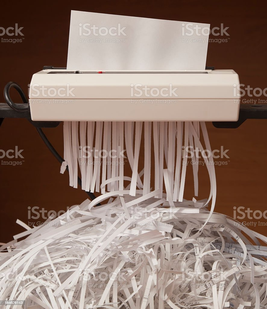 A paper shredder with pile of shreds beneath stock photo