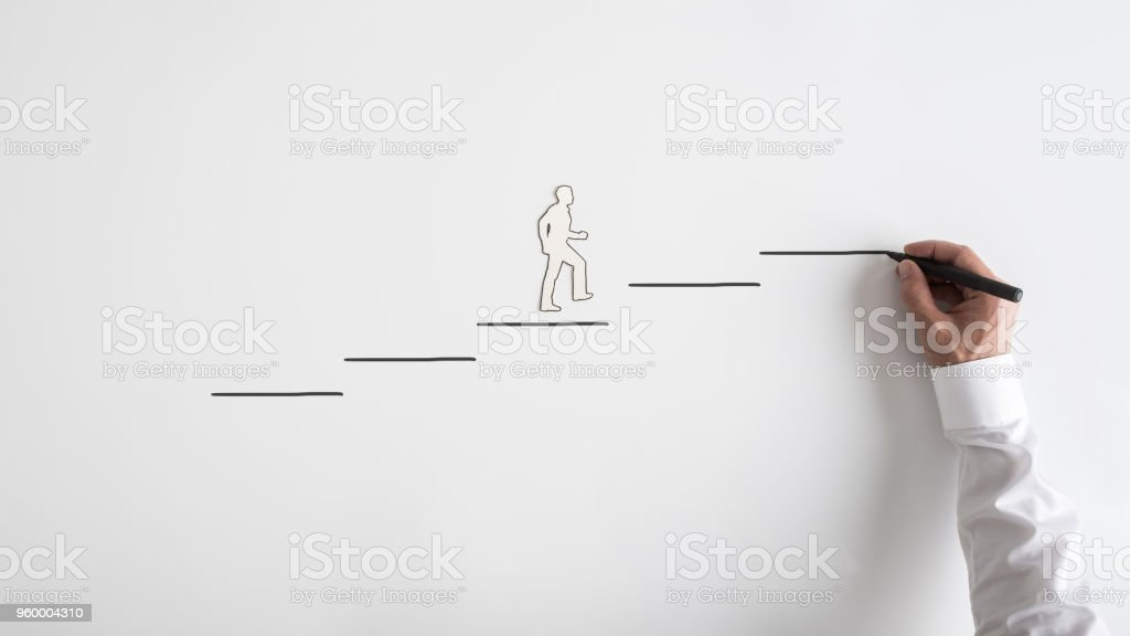 Paper silhouette cutout of a man and a businessman drawing steps stock photo