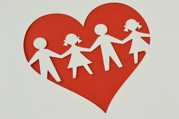 Paper silhouette of children in a heart - Child protection and love concept Paper silhouette cut of children chain in a heart - Child protection and love concept social responsibility stock pictures, royalty-free photos & images