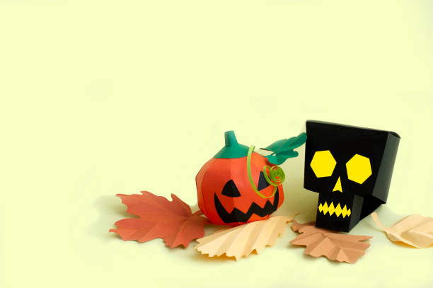 Paper skull and Jack-o-lantern with autumn leaves stock photo