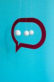 istock Paper speech bubble balls and bullet pendulum float against blue background 1225192657