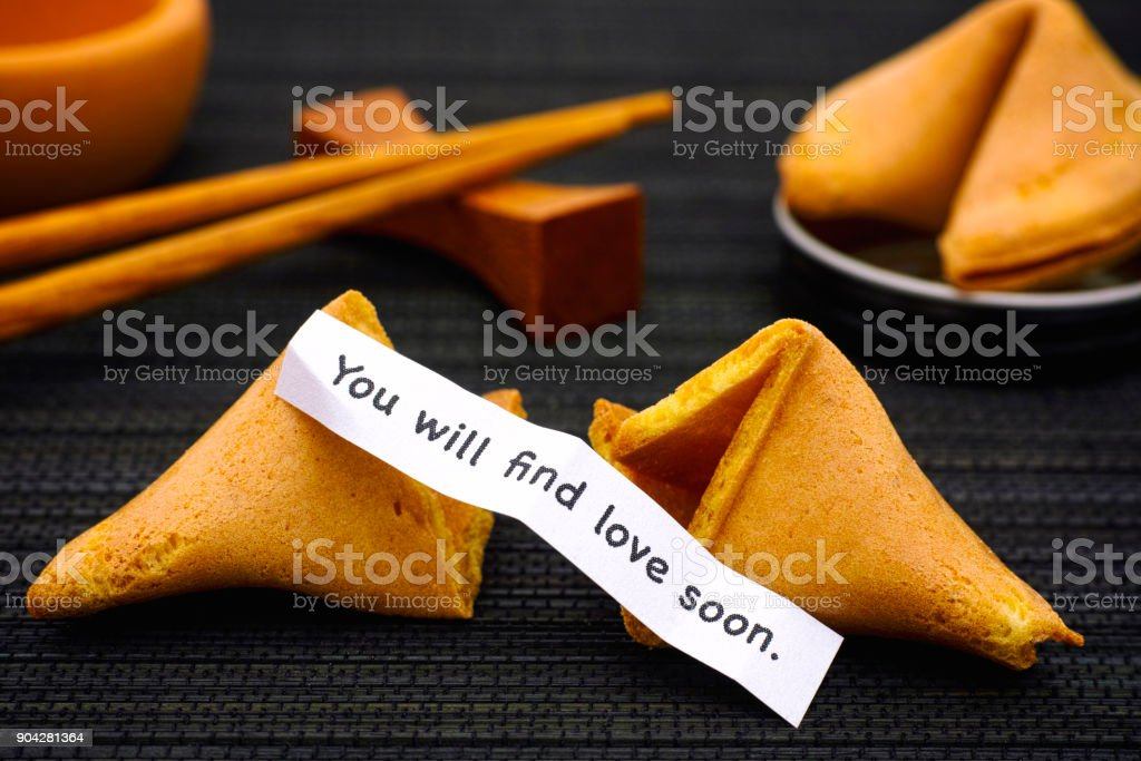 Paper strip with phrase You will find love soon. from fortune cookie, another cookie and chopsticks on black napkin background. stock photo