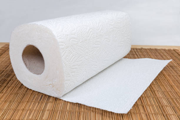 Paper towels roll with tear sheets on bamboo table mat stock photo