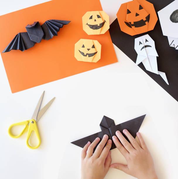papierspielzeug origami für halloween. händen der kinder.  vorbereitung auf den feiertag. - origami anleitungen stock-fotos und bilder