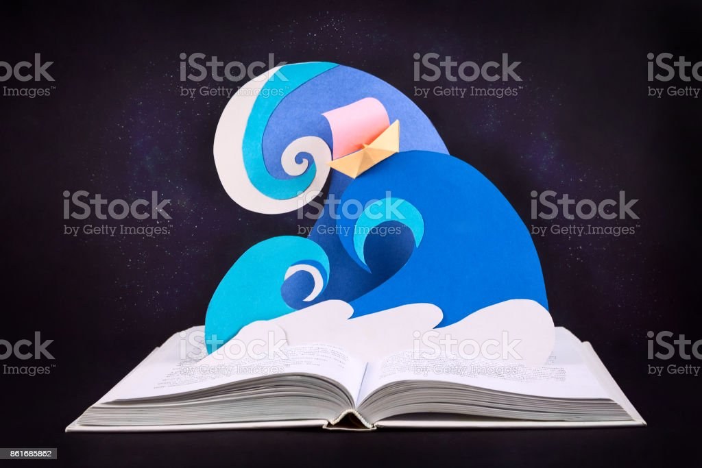 Paper waves and boat coming out of opened book. Papercraft. Concept of reading and magic inside of a book. Selective focus. stock photo