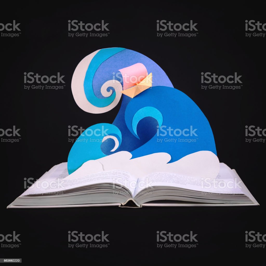 Paper waves and boat coming out of opened book. Papercraft. Concept of reading and magic inside of a book. Selective focus. Square stock photo