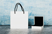 Paper white bag with a cup of coffee on a gray and blue background. Close up. Place for text. Mock up concept for gift wrapping.