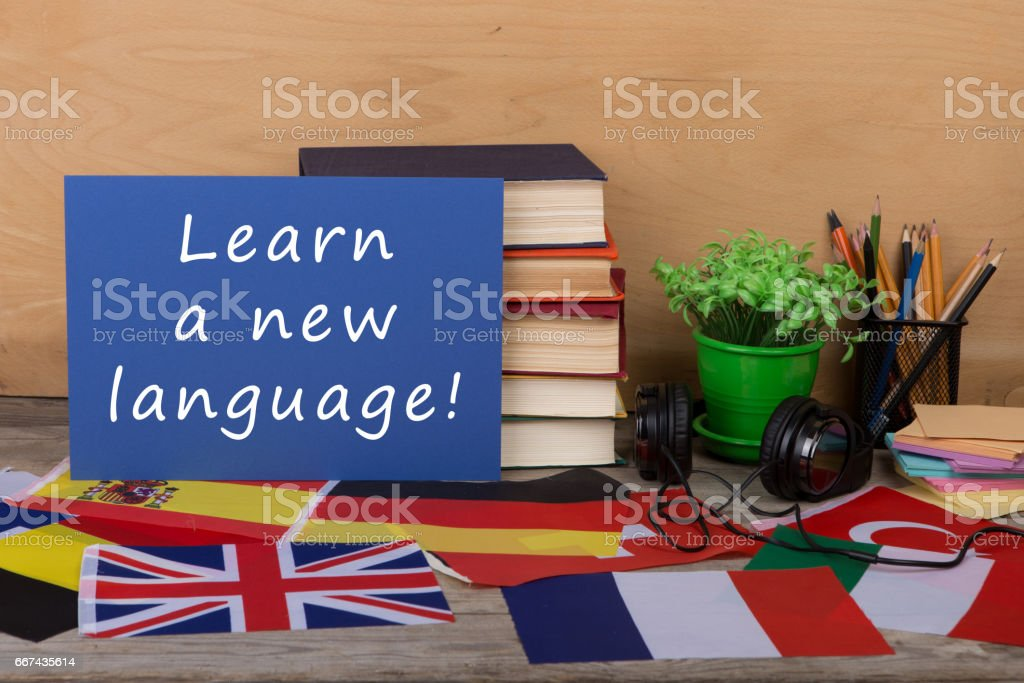 paper with text 'Learn a new language!', flags, books, headphones stock photo