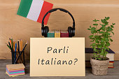 paper with text 'parli italiano?', flag of the Italia, books