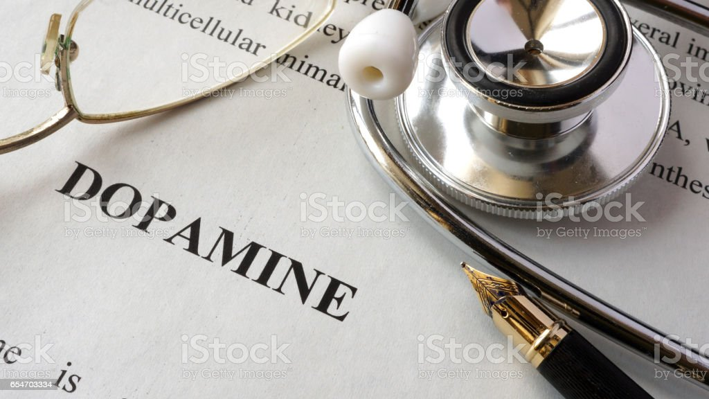 Paper with word Dopamine and a book. stock photo