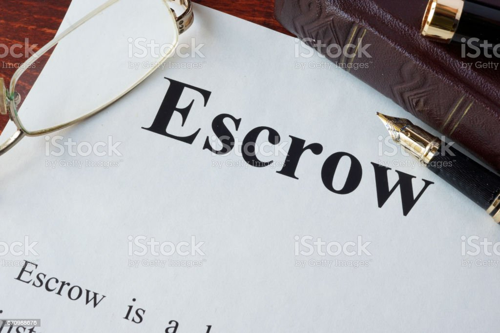 Paper with word Escrow and glasses on a table. stock photo