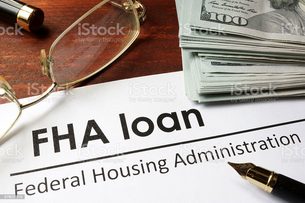 Paper with words fha loan on a wooden background. stock photo