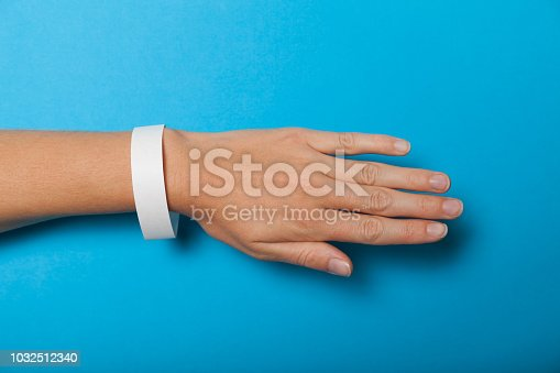 Paper wristband mockup, event bracelet on hand. Empty ticket wrist band design.
