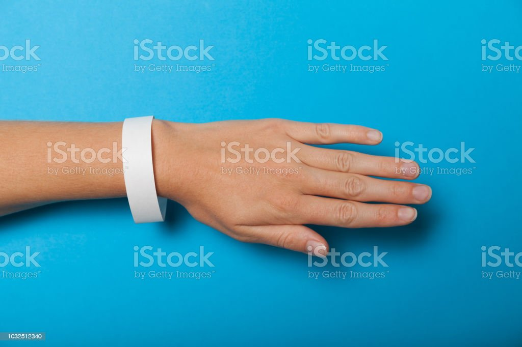 Paper wristband mockup, event bracelet on hand. Empty ticket wrist band design stock photo