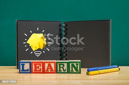 istock Paper yellow light bulb shine on over Learn wood block and black notebook on wood table with green blackboard wall,Education concept 860313600