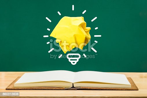 istock Paper yellow light bulb shine on over open white notebook on wood table with green blackboard wall,Education concept 860313606