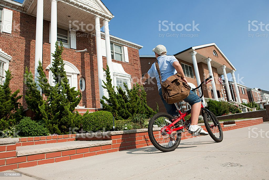 Paperboy with bike throwing newspaper stock photo