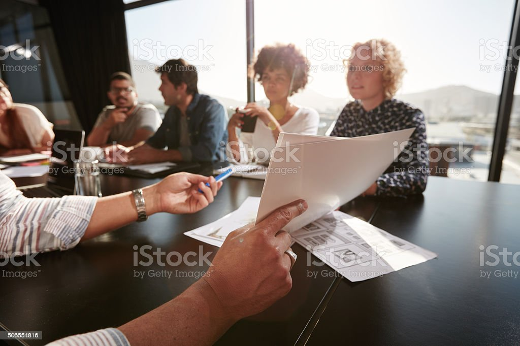 Papers in hands of man explaining plan to creative team stock photo