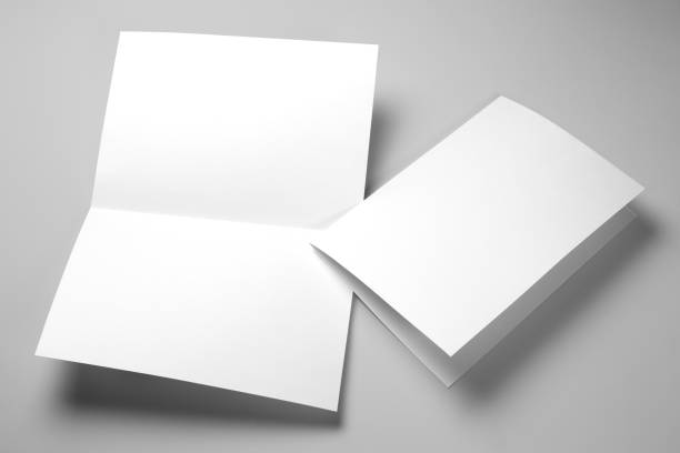 Papers on gray Blank half-folded booklet, postcard, flyer or brochure mockup template on gray background folded stock pictures, royalty-free photos & images