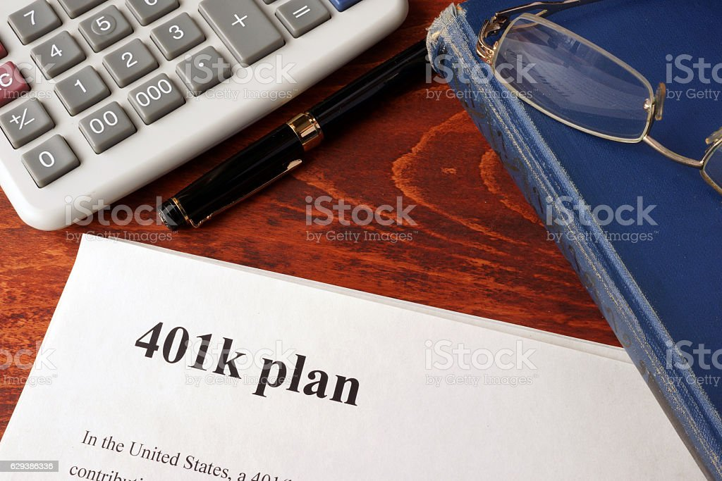 Papers with 401k plan and book on a table. stock photo