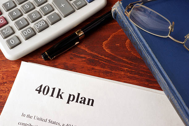 Papers with 401k plan and book on a table. Papers with 401k plan and book on a table. 401k stock pictures, royalty-free photos & images
