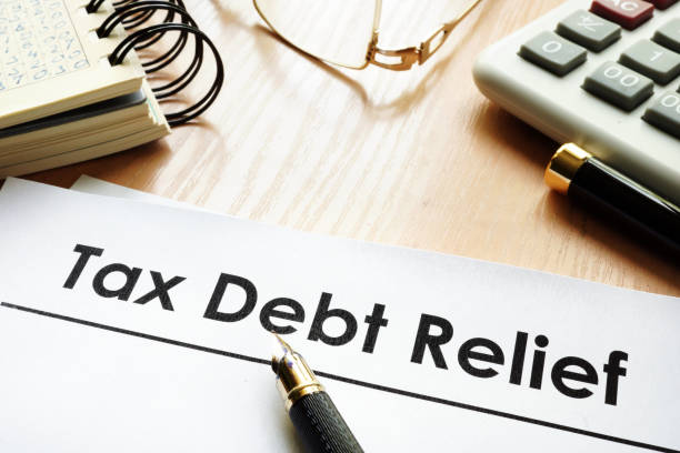 Papers with title tax debt relief on a desk. stock photo