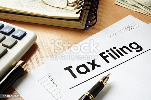 istock Papers with title Tax filing on an office desk. 874826692