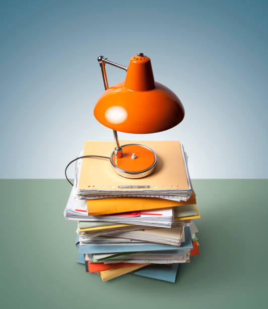 Paperwork. A stack of file folders under a lamp. Photo with clipping path. stock photo