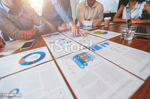Paperwork and hands on a board room table at a business presentation or seminar. The documents have financial or marketing figures, graphs and charts on them. There is a digital tablet and laptop on the table. Multi ethnic group including Asian, Caucasian and African American.