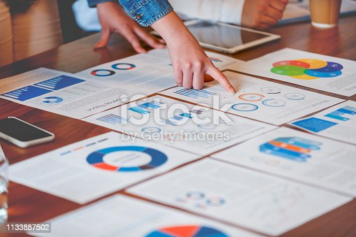 Paperwork and hands on a board room table at a business presentation or seminar. The documents have financial or marketing figures, graphs and charts on them. There is a digital tablet and laptop on the table