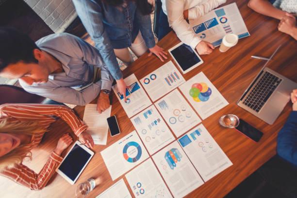 Papierkrams und Hände auf einem Vorstandsetafel bei einer Geschäftspräsentation oder einem Seminar. Die Dokumente haben Finanz-oder Marketingzahlen, Grafiken und Diagramme. Auf dem Tisch stehen ein digitales Tablet und Laptop. Multikultursche Gruppe, ei – Foto