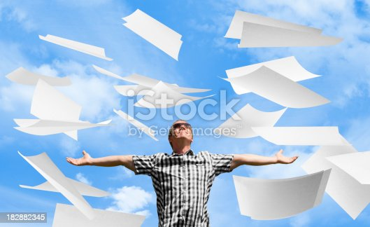 157312920 istock photo Paperwork thrown in air by man with arms outstretched 182882345