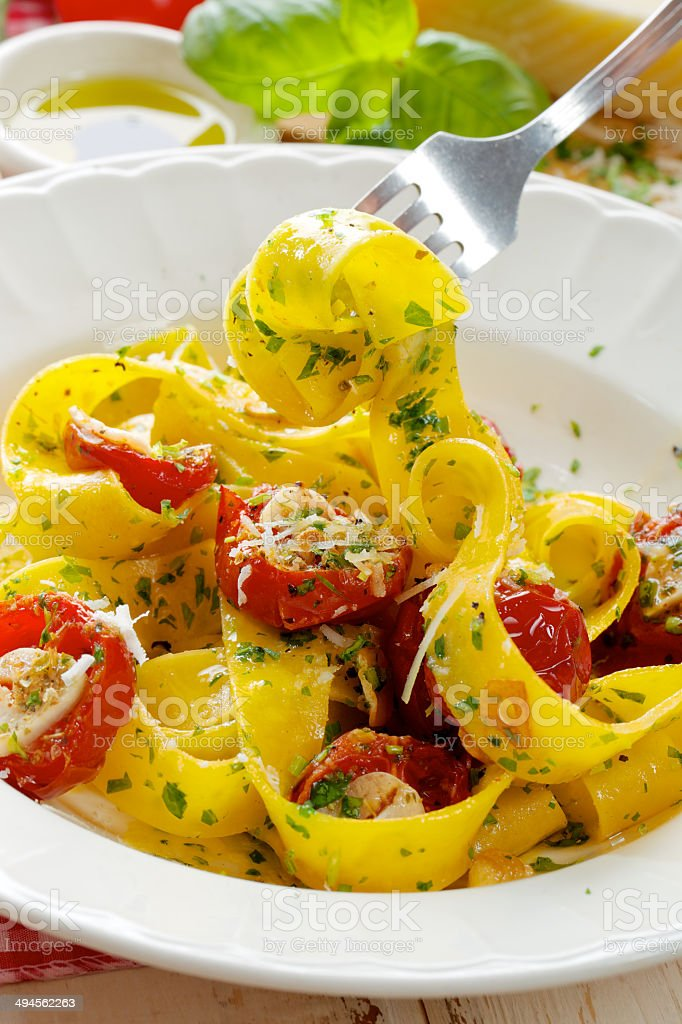 Pappardelle pasta with tomatoes, herbs and Grana padano cheese stock photo
