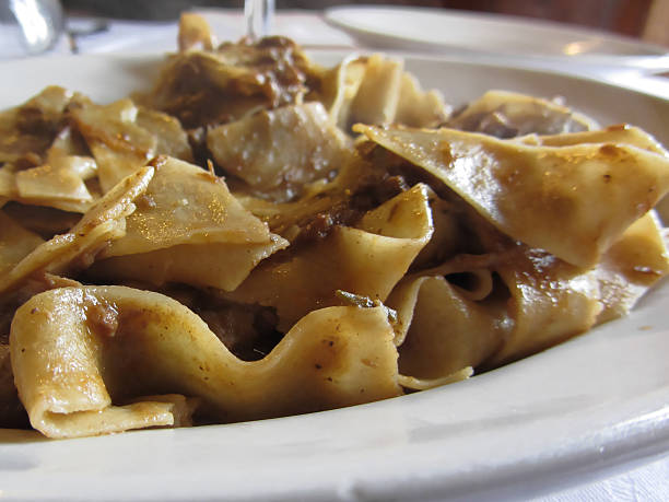 Pappardelle with boar ragu. Tuscan typical recipe of italian pasta Pappardelle with boar ragu. Tuscan typical recipe of italian pasta ragout stock pictures, royalty-free photos & images