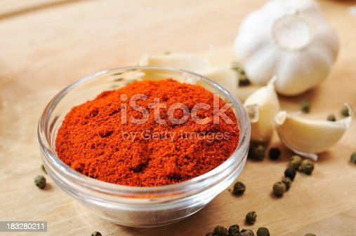close up of ground paprika in the glass dish on the table with few pepper seeds and garlic pieces aroundsee other similar images: