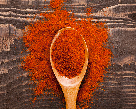 Close up of ground paprika in wooden spoon on wooden background; Adobe RGB color space;