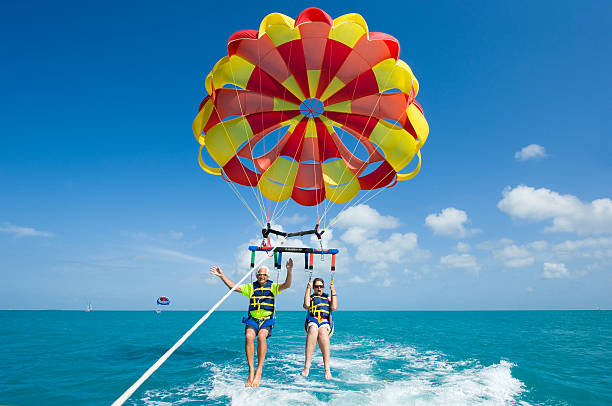 People On A Parachute Behind The Boat - Parasailing Stock