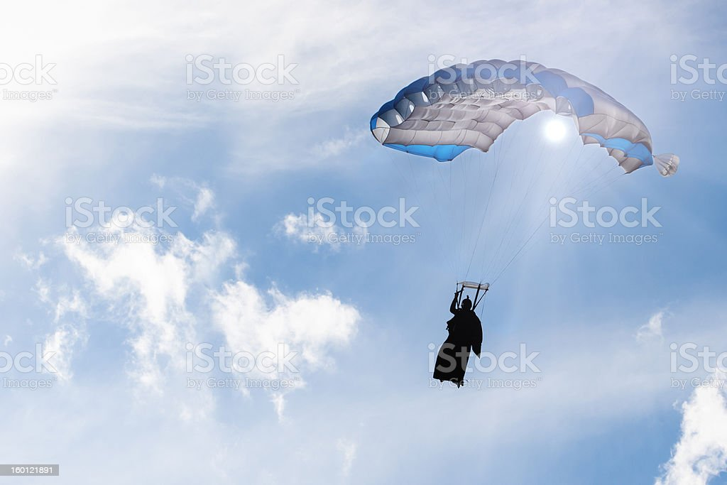 Parachute at sky under sun rays, skydiver silhouette in wingsuit. stock photo