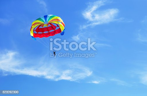 Parachute jumping. Colorful parachute is in the sky, under the clouds. Copy space. Empty place for message. Outdoor. Travel, freedom, adventure, success, business concept.