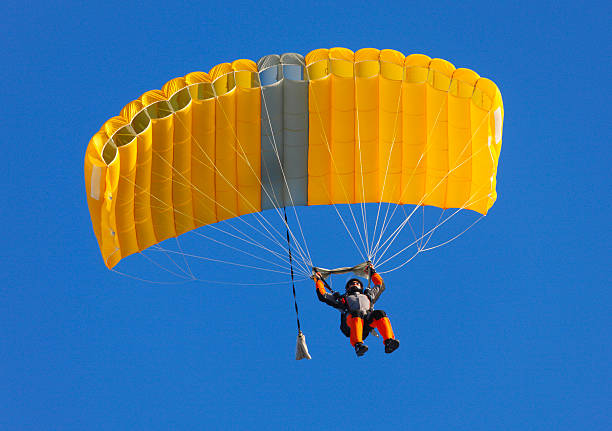 Parachute on a clear blue sky  Skydaiver parachuting stock pictures, royalty-free photos & images