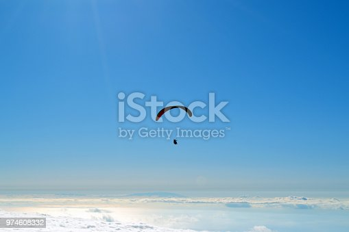 Paraglider flying over clouds in a summer day