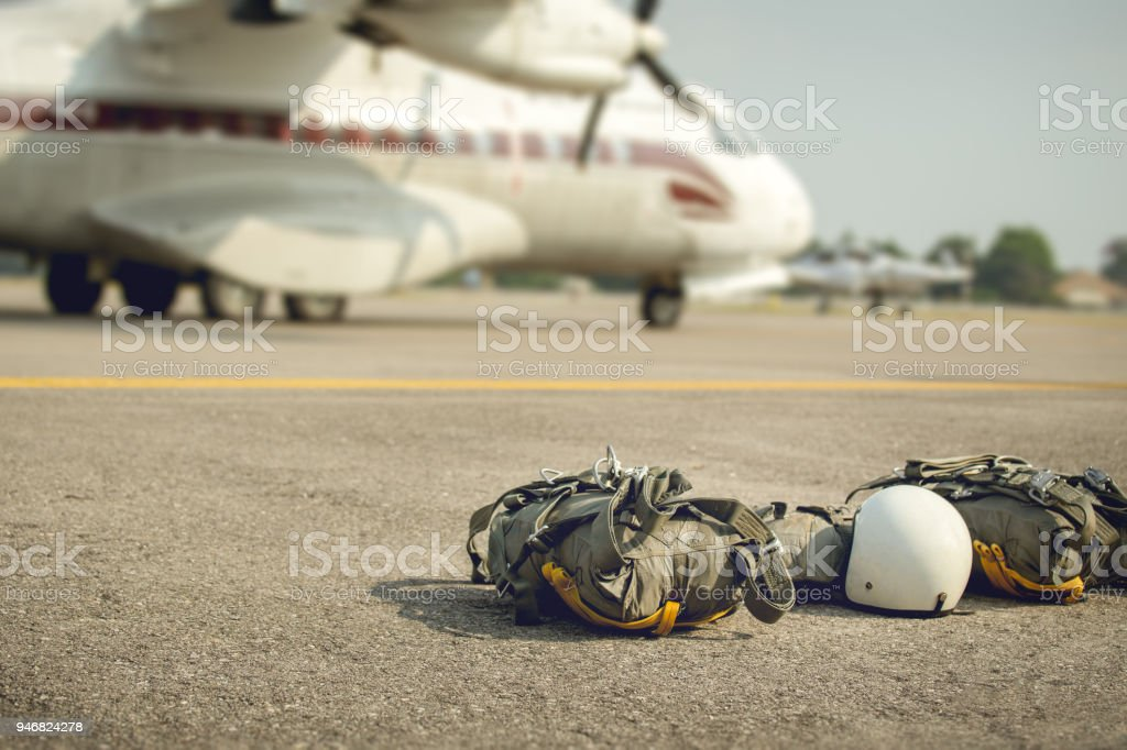 Parachute with equipment for paratroop on ground and military transport aircraft background in cinematic tone stock photo