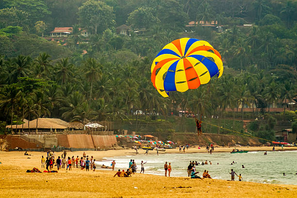 parachuter gliding over a populated beach Candolim, Goa, India - February 15, 2013: Tourists are para-sailing in the sunny sea side of Calangute Beach goa stock pictures, royalty-free photos & images