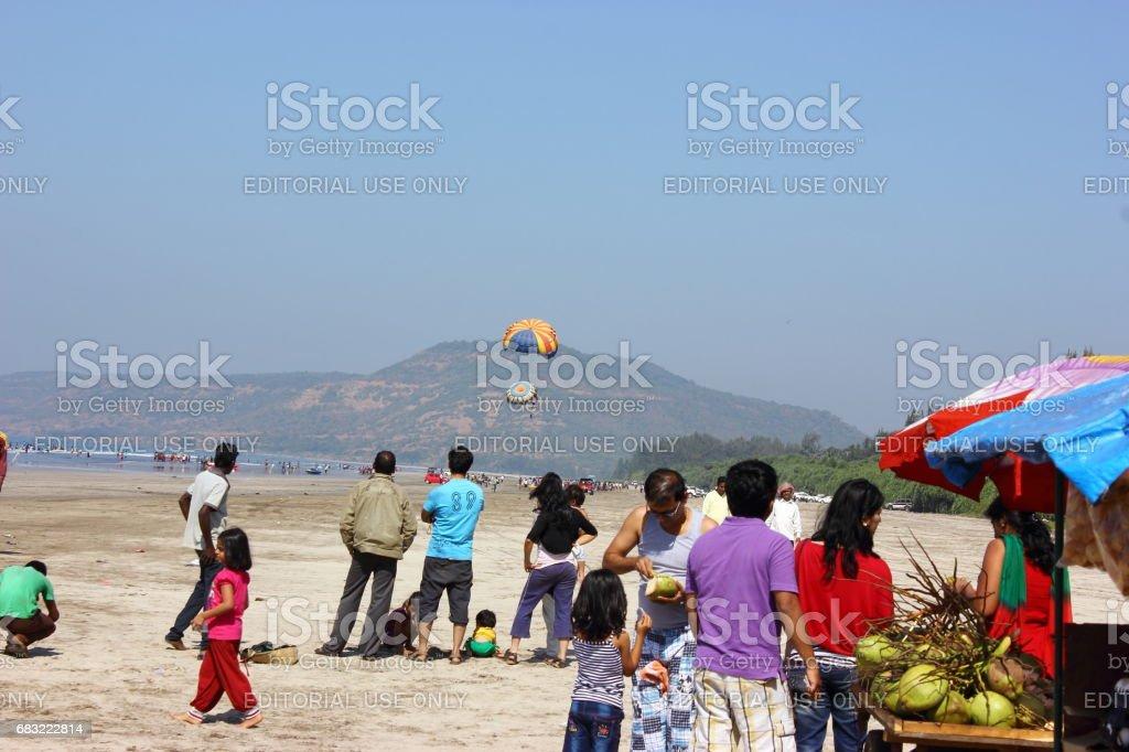 Parachuter gliding over a populated beach foto de stock royalty-free