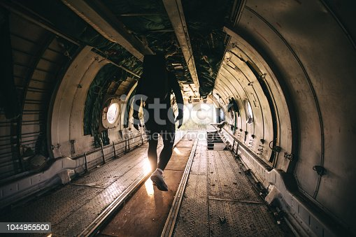 Handsome and athletic man with a bag on his back, standing in a abandoned airplane.